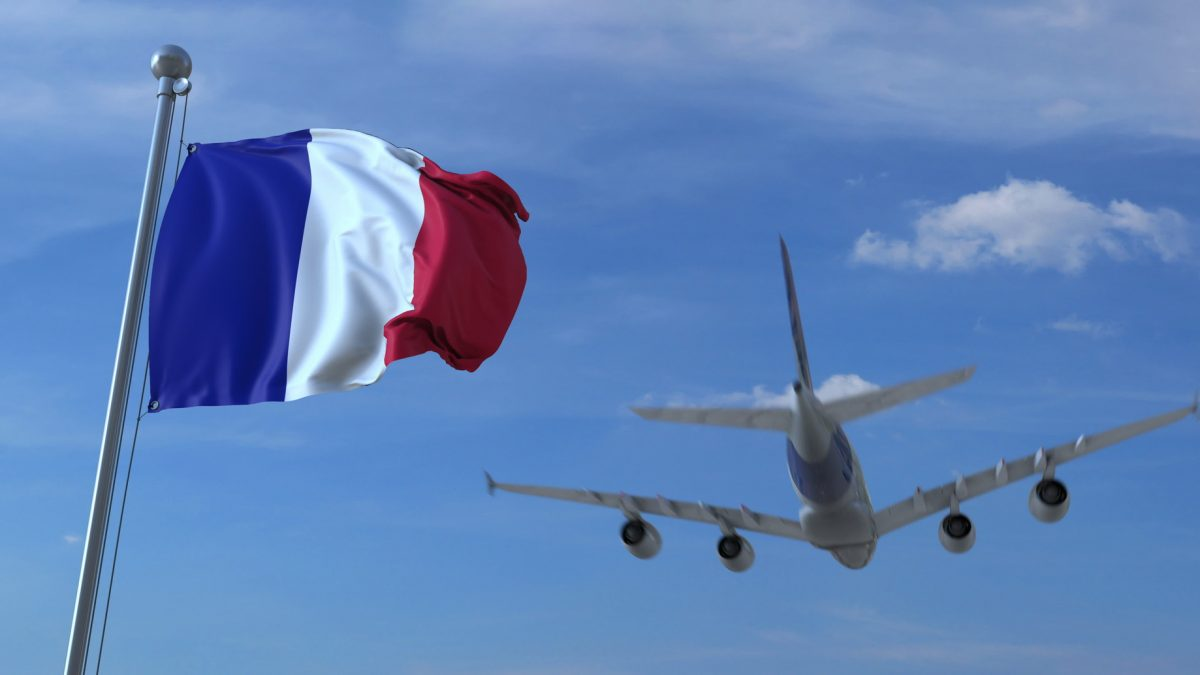 airplane landing in France behind the French flag